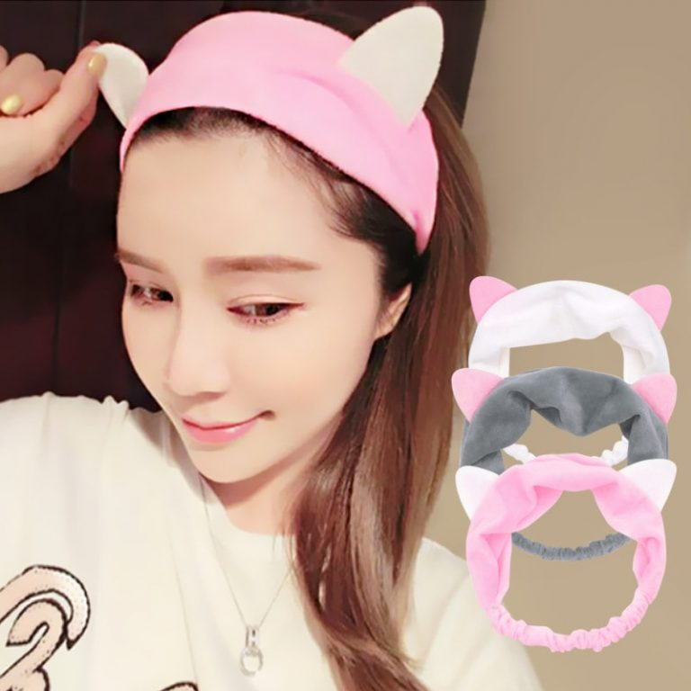 A beautiful, smiling girl wearing a make-up headband shaped as cat ears