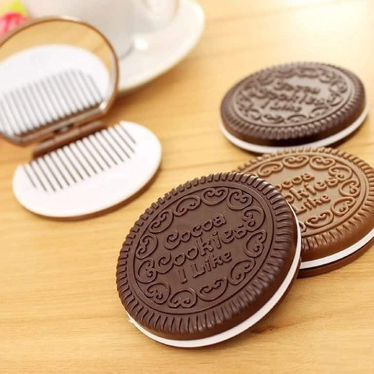 Four cookie-shaped mirror & hair comb sets on a wooden table