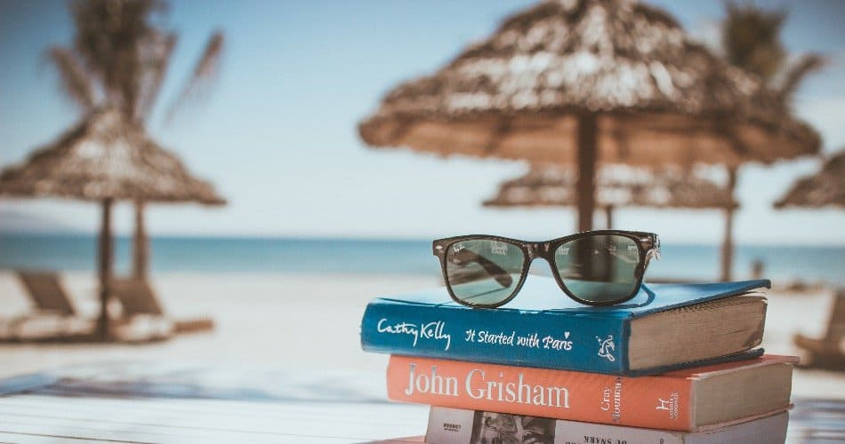 Three books and a pair of glasses on a beach