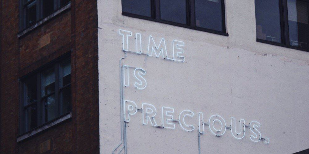 """""""Time is precious"""" sign on a building's wall"""