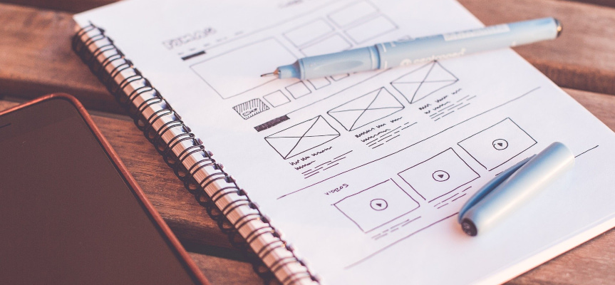 Website layout sketch in a notebook